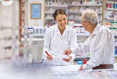 A young pharmacist helping an elderly customer at the prescription counter.