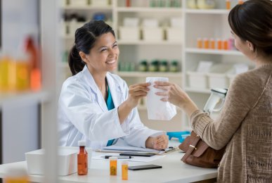 Friendly pharmacist hands a paper bag to young female customer at the checkout counter