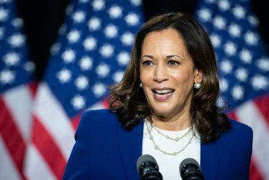 Vice President Harris wears a blue blazer in front of three American flags as she announces her candidacy for Vice President in Wilmington, Delaware