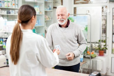Happy senior male customer buying medications at drugstore